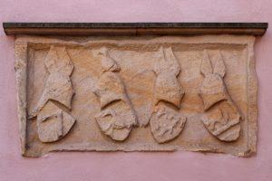 Der Wappenstein auf der Rückseite des Obernburger Rathauses zeigt die Wappen der Eltern von Jorg Bache und seiner Frau Agnes, geb. von Erlenbach. Ursprünglich dürfte er über dem Tor der Bacheburg angebracht gewesen sein.