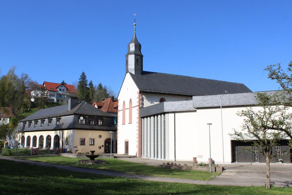 """Drei Epochen, ein Ensemble: Die ehemalige Klosterkirche aus dem 12. Jahrhundert, eingerahmt von der sogenannten """"Remise"""" aus dem 18. Jahrhundert links und dem Kirchenanbau aus den 1970er Jahren rechts."""