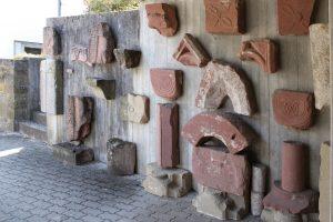Diese Fragmente der hochwertigen Bauausstattung kamen bei der Ausgrabung zutage. Heute sind sie etwas versteckt an einer Wand auf der Nordseite der Kirche angebracht.